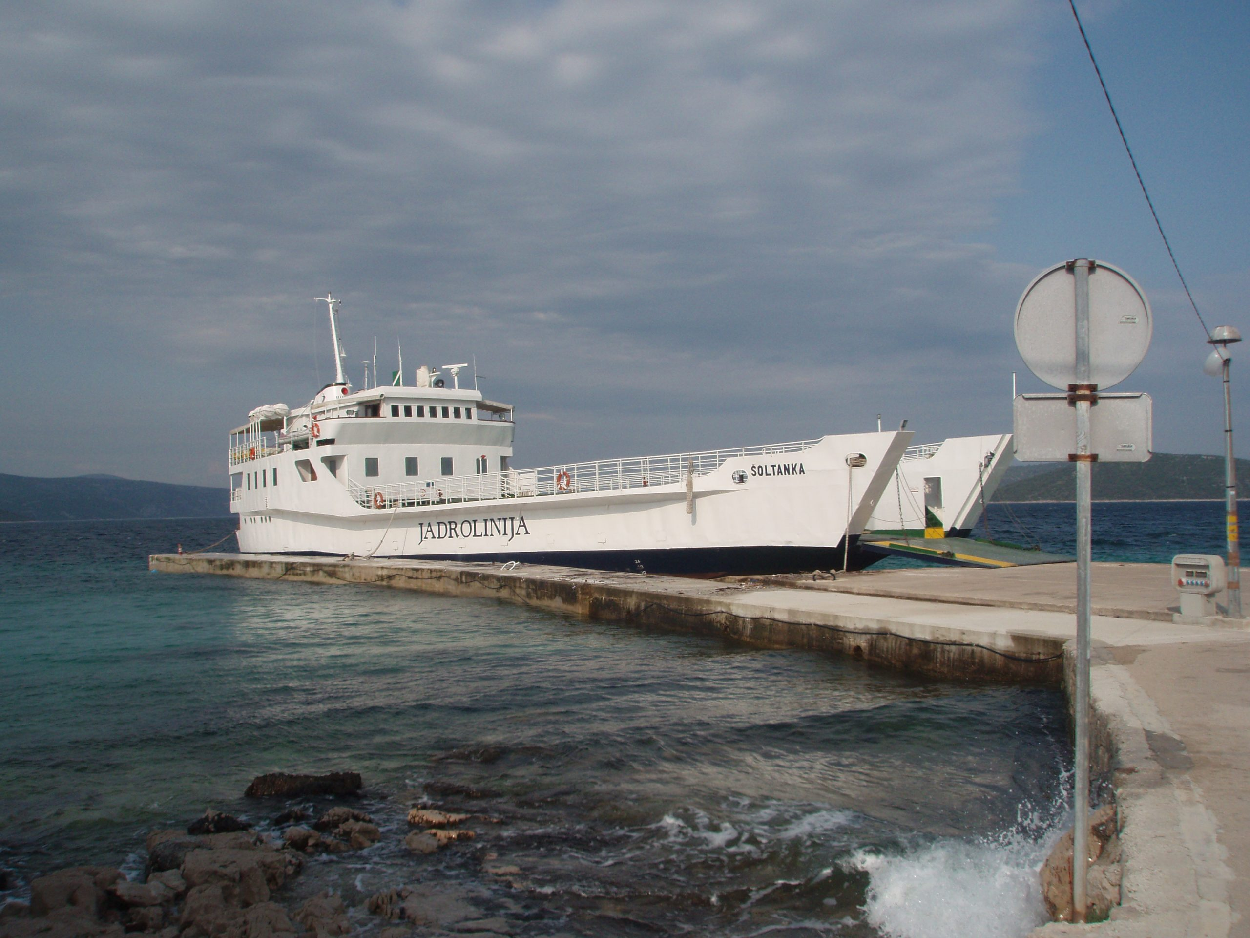 Šoltanka ferry at the dock on Drvenik Mali. On a Monday in May, the ferry carried Croatian vacationers, retired people, construction workers, and the priest from Trogir, who was rehearsing his sermon leaning over the railings, book in hands, reading out to the waves. He was the first to jump off the ferry, hurrying toward the nearby church as the ship was leaving the island in an hour, and he had to be on it.