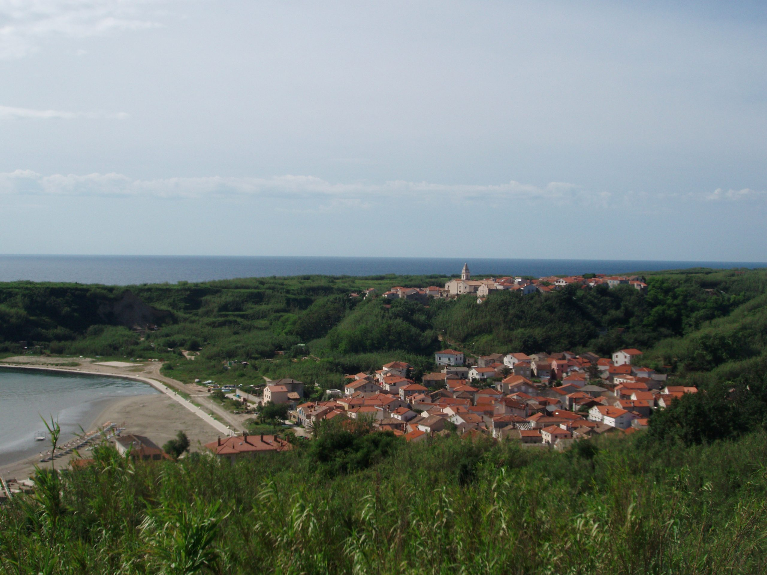 The upper and lower village of Susak, the island made of reed and sand, as seen from the path that leads toward the Susak Lighthouse. The lighthouse was built in 1881, and has been run by the same family for over thirty years now. They tend to the light, their garden, and their cats.