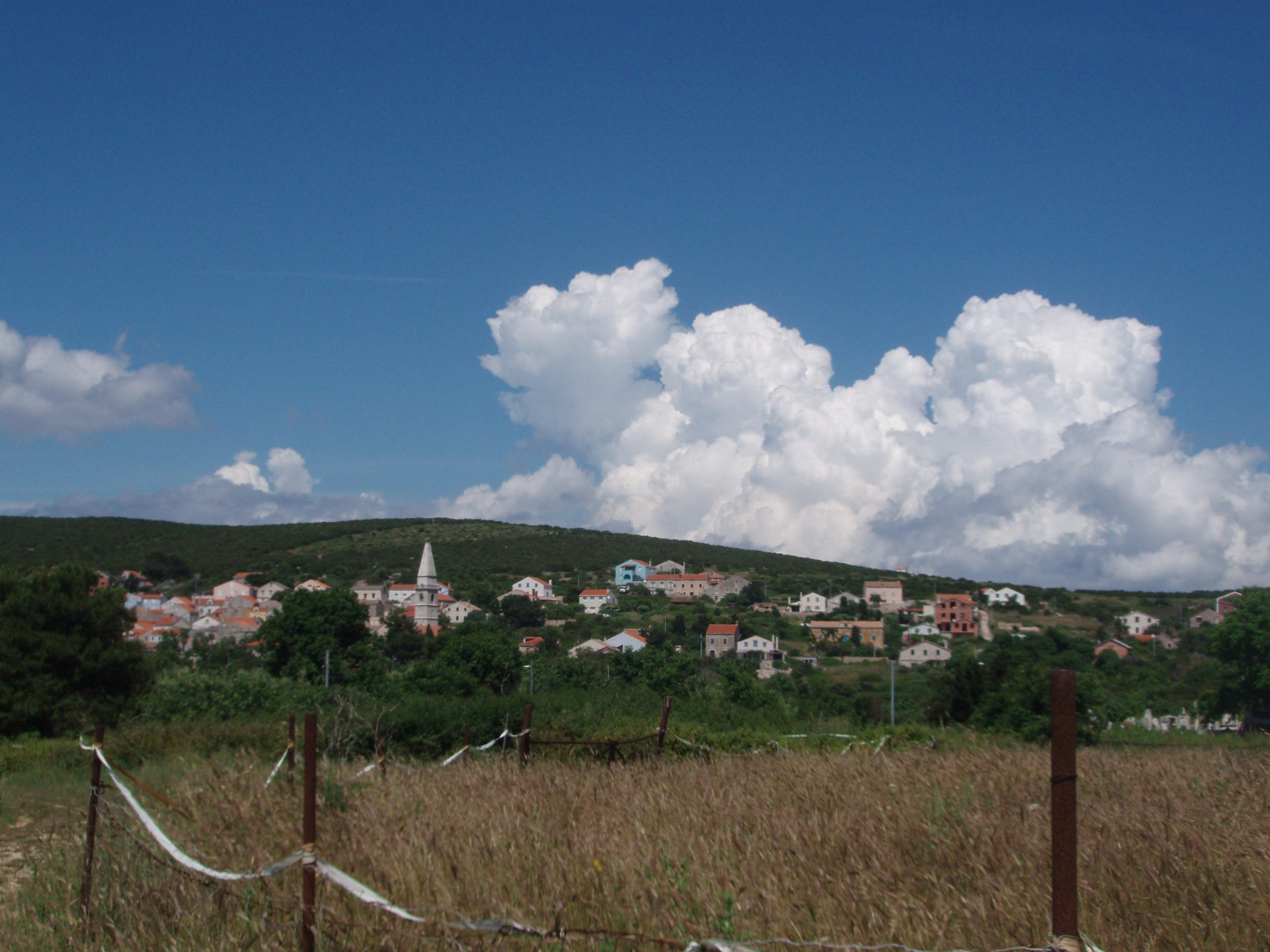 Clouds towering above the only settlement on Unije, the island that boasts a small airport.