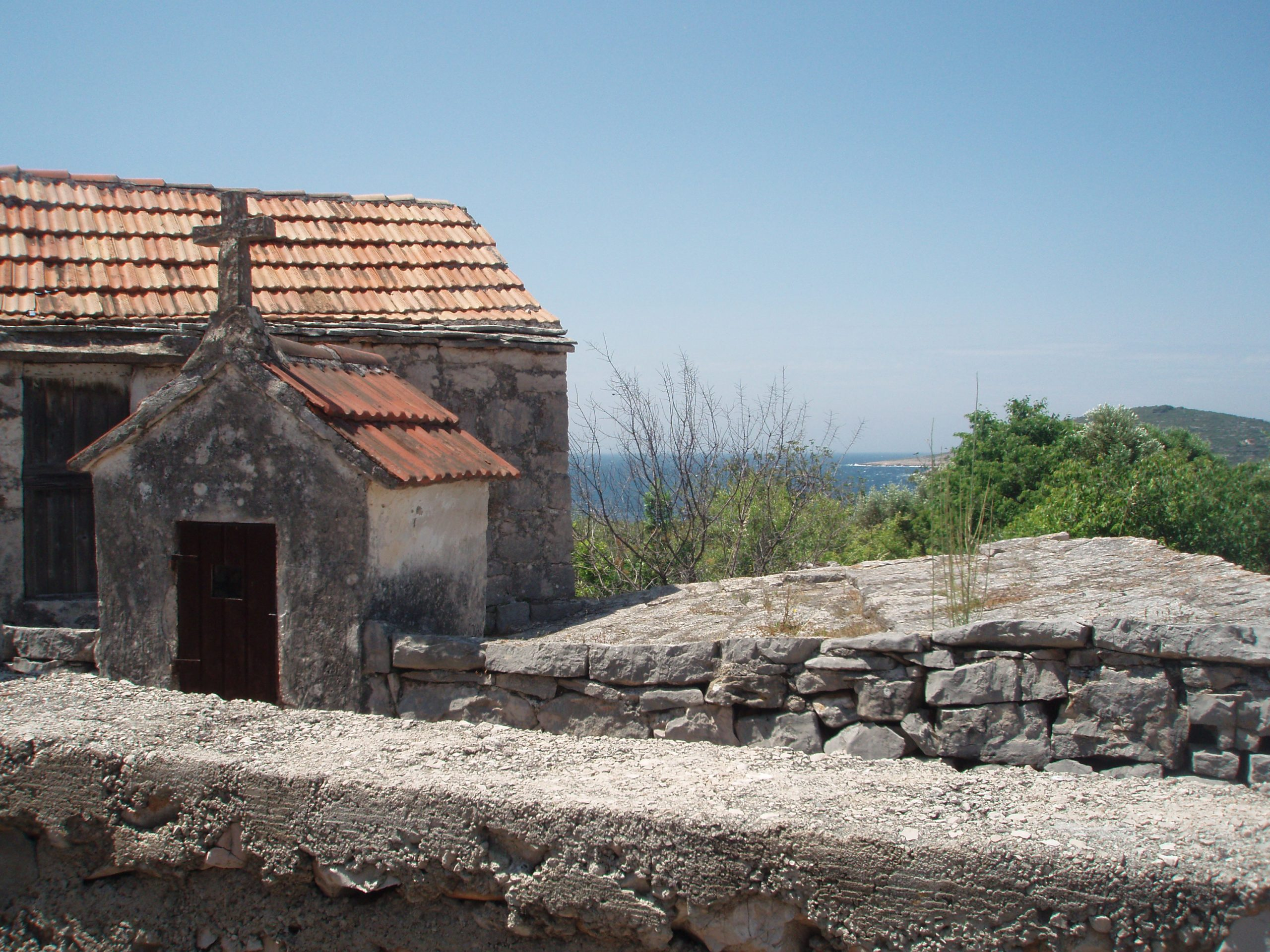 A scene from the almost deserted village of Petomavar above the cove of Vela Rina. Sealed and dried-up water tanks and torn-down stone walls, with macchia breaking out through the glassless windows, surround the few inhabited homes.