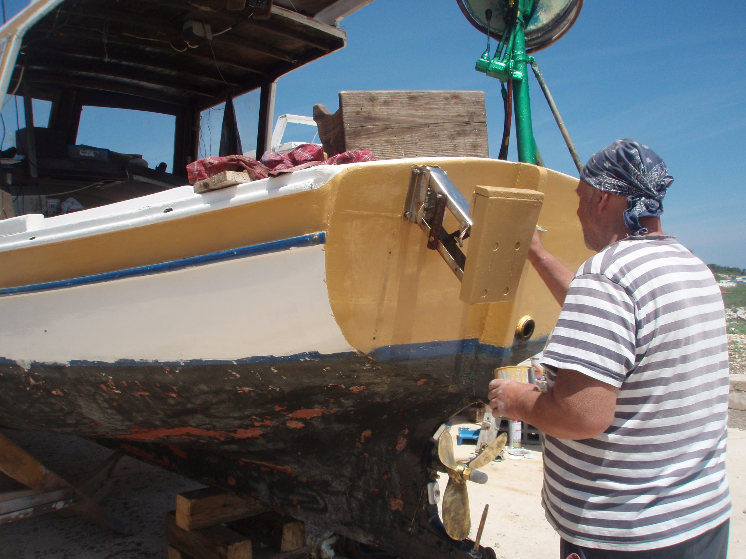 """In front of the Sports and Fishing Association """"Galeb"""" (Seagull) in the harbour of Mul on Silba, members run a makeshift shipyard. We came to Silba just in time for the first briškula tournament organized in Galeb, followed by grilled fish and sausages, and wine """"from the shop""""."""