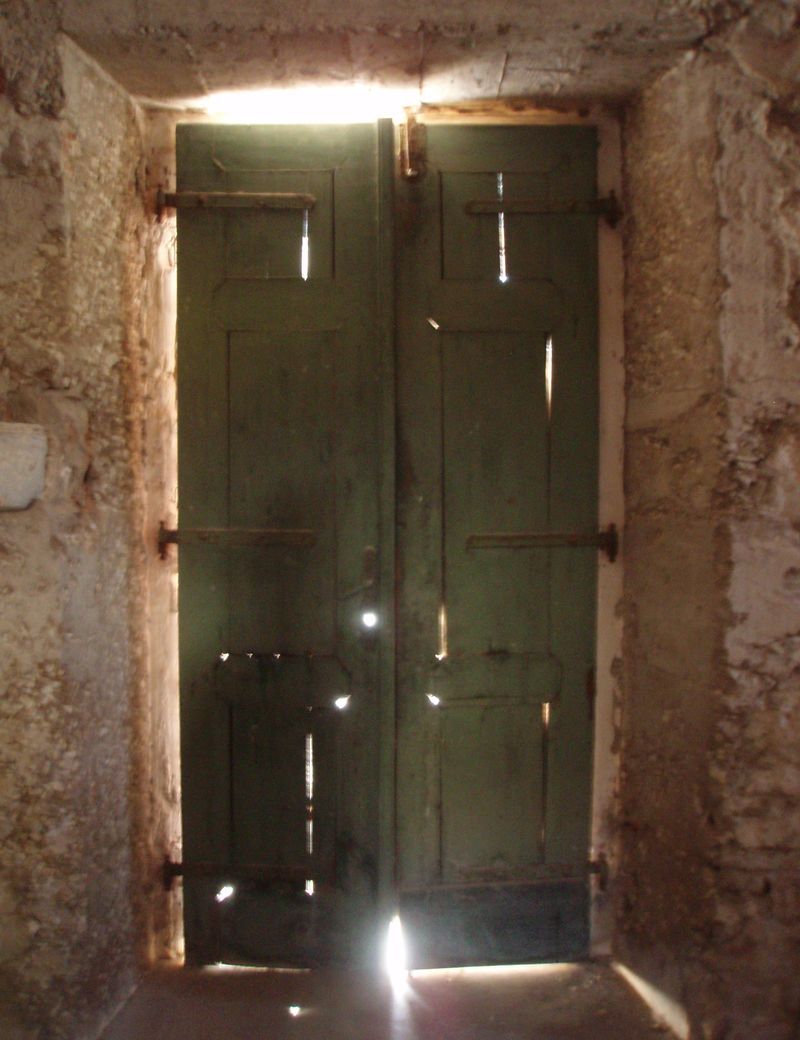 Inside the serene but dilapidated, and out-of-function seventeenth-century Church of St. Mary of Karmel on Silba. The fierce afternoon light is breaking in through the cracked wooden door.