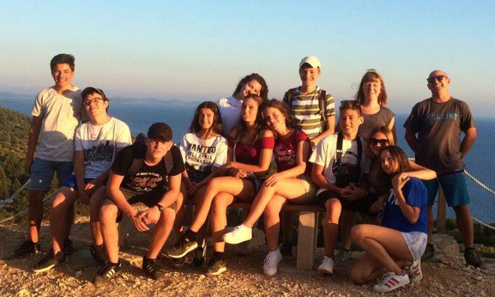 American-Croatian helping locals improve English writing skills on anoutdoor adventure